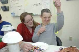 Megan Lamphear (Journeys Program Manager) admires the necklace that Andre Kish has created, during a typical day at the new Journeys facility in Bloomingdale.