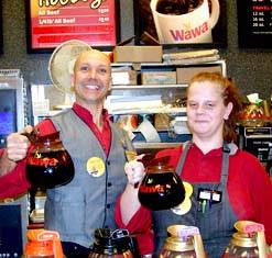 Two wawa employees holding up coffee pots smiling