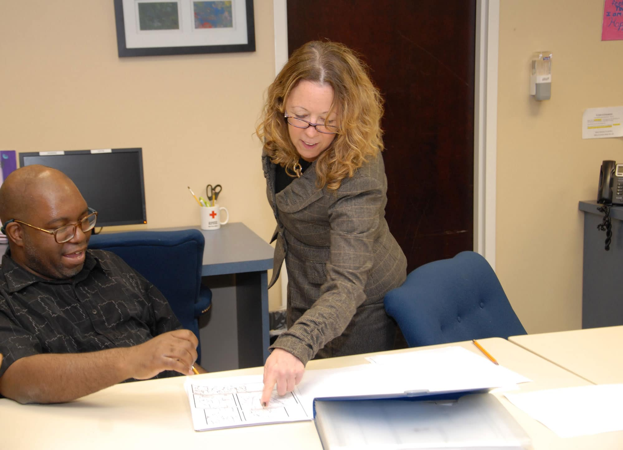 Eddie W., an employee at the Daily Plan It in Princeton, shows Elizabeth Connolly his comic book drawings.
