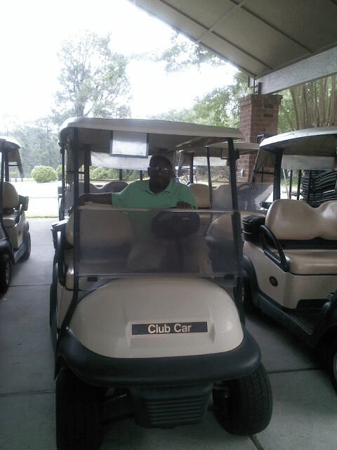 Clarence driving a golf cart around