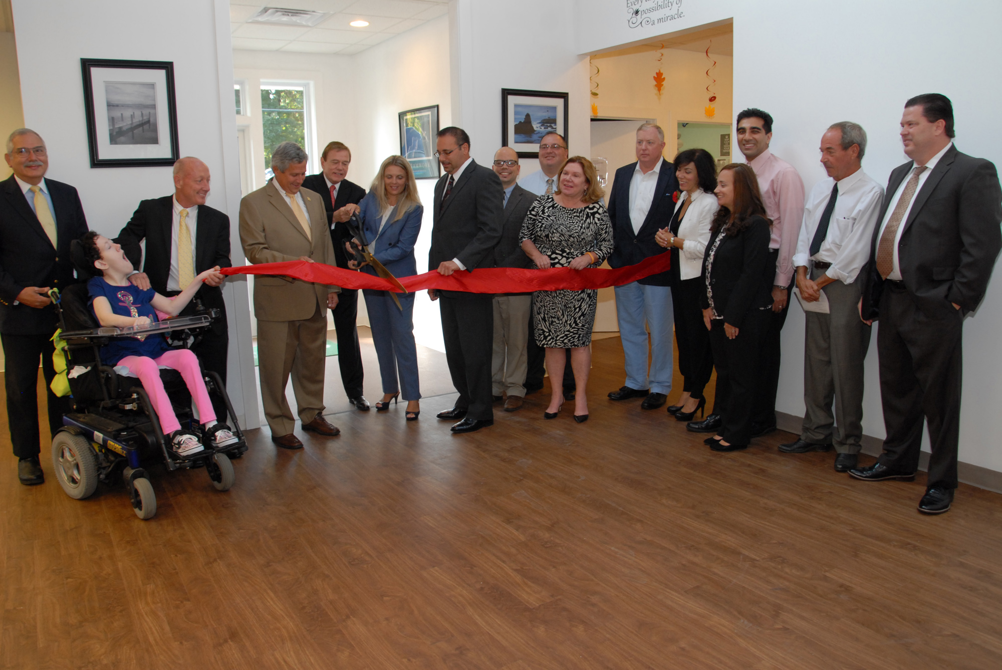 From left: Philip Lian, COE Board member; Kimberly Spano; James Spano, COE Board member; Senator Christopher 'Kip' Bateman; Robert Stack, President and CEO of Community Options, Inc.; Svetlana Repic-Qira , Community Options, Inc. Regional Vice President of New Jersey;Anthony Ferrera, Administrator/Deputy Township Clerk for Hillsborough Township; David Kois, Business Advocate for Hillsborough Township; Daniel Surtz, COE Board Member; Gail Gordon, COE Board Member; Alec Taylor, COE Board Member; Linda Thomas, member of the Red Ribbon Academy's Parent Group; Dr. Baber Ghauri, COE Board Member; Courtney Eidel, Chief Administrative Officer of Community Options, Inc.; Paul Hritz, COE Board Member and David Sweeney, Chief Financial Officer of Community Options, Inc open the new Red Ribbon Academy in Hillsborough, NJ.