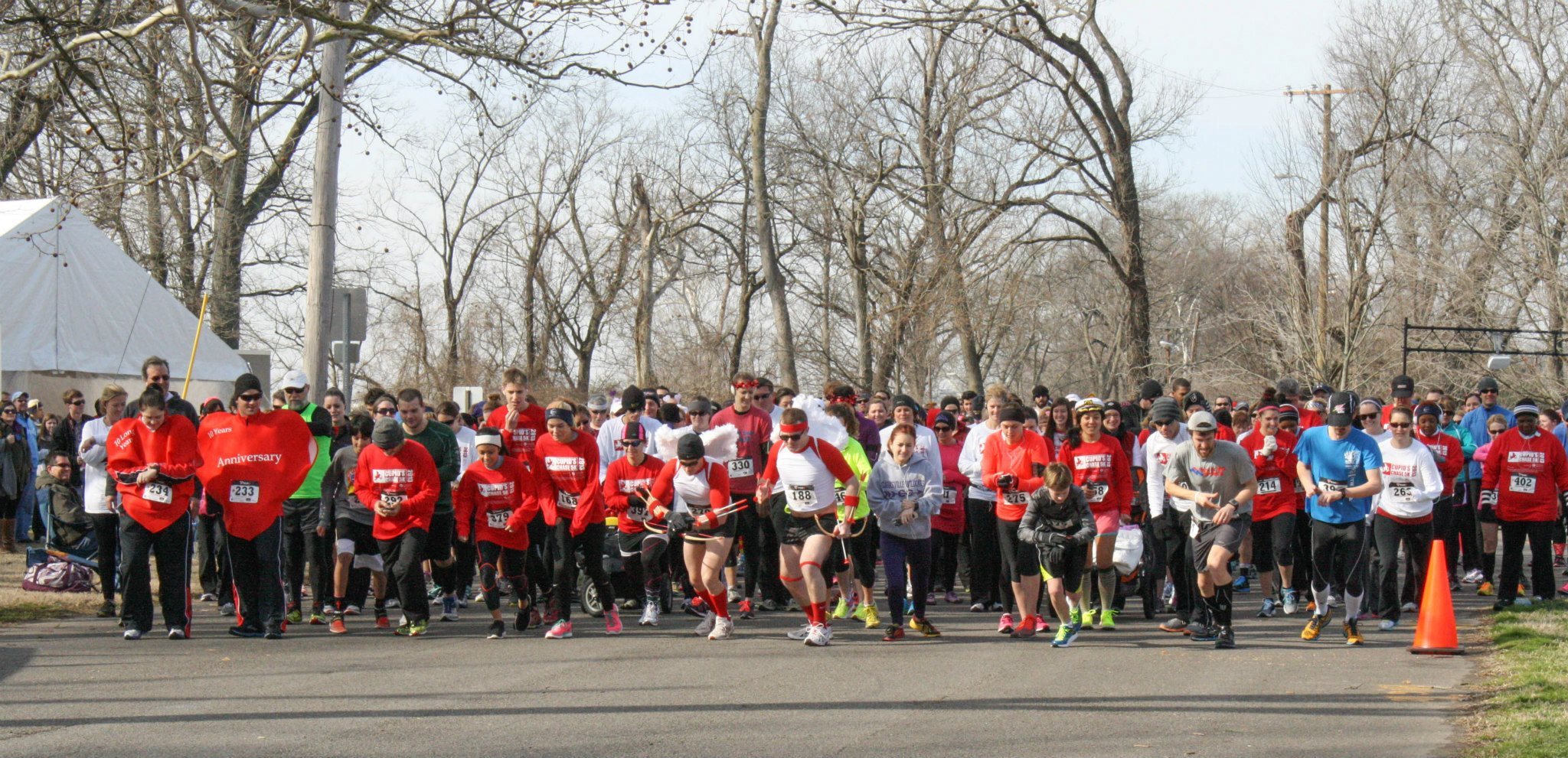 A group of runners starts a past Cupid's Chase 5K race. Participants in the race where different colored shirts denoting whether they are 'unavailable' or 'available.'