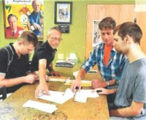 Marc Boyle and Kevin McElhinny volunteer for the Greater Latrobe Laurel Valley Regional Chamber of Commerce stuffing envelopes as part of the Community Integration program. Assisting are Ryan Browne, direct support professional, and Jeff Minkovich, Comm.unity Integration counselor at the Chantber. Photo by Ernie Sistek