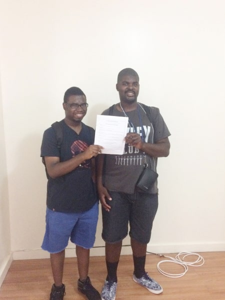 Keith Baxter-Young and Andrew Daniels hold up the lease agreement to their new place they moved to in July.