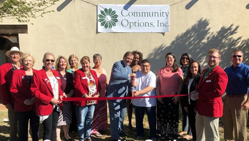 Pictured in the center are Robert Stack, President and CEO of Community Options, and Mark Matos, supported by Community Options Amarillo, cutting the ribbon to the new Day Habilitation program in Amarillo, Texas. Also pictured are Community Options staff and members of the local Chamber of Commerce.