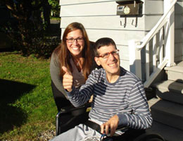 Two smiling people outside of a home. The person who is sitting in a wheelchair has his thumb up while the woman behind is leaned in close.