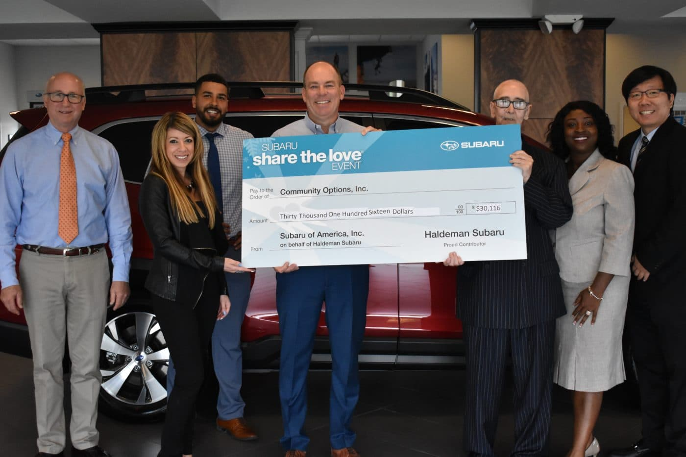 From left to right: Greg Hritz, Mike Manna, Kim Schleyer, Scott Haldeman, Joseph Everett, Ida Bormentar, and Andrew Park as they are presented a check from Haldeman Subaru representatives of Community Options, Inc. on May 23.