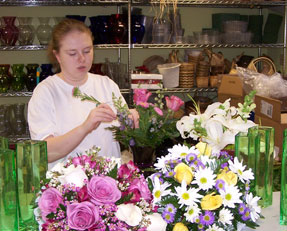 Working at vaseful creating a floral arrangement