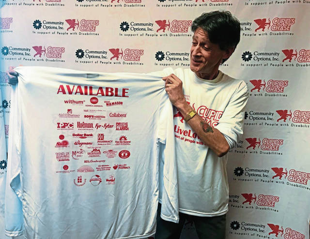 Jeffrey Minkovich, who helps organize the Cupid's Chase charity run for nonprofit Community Options in Hempfield, displays a T-shirt participants will receive.