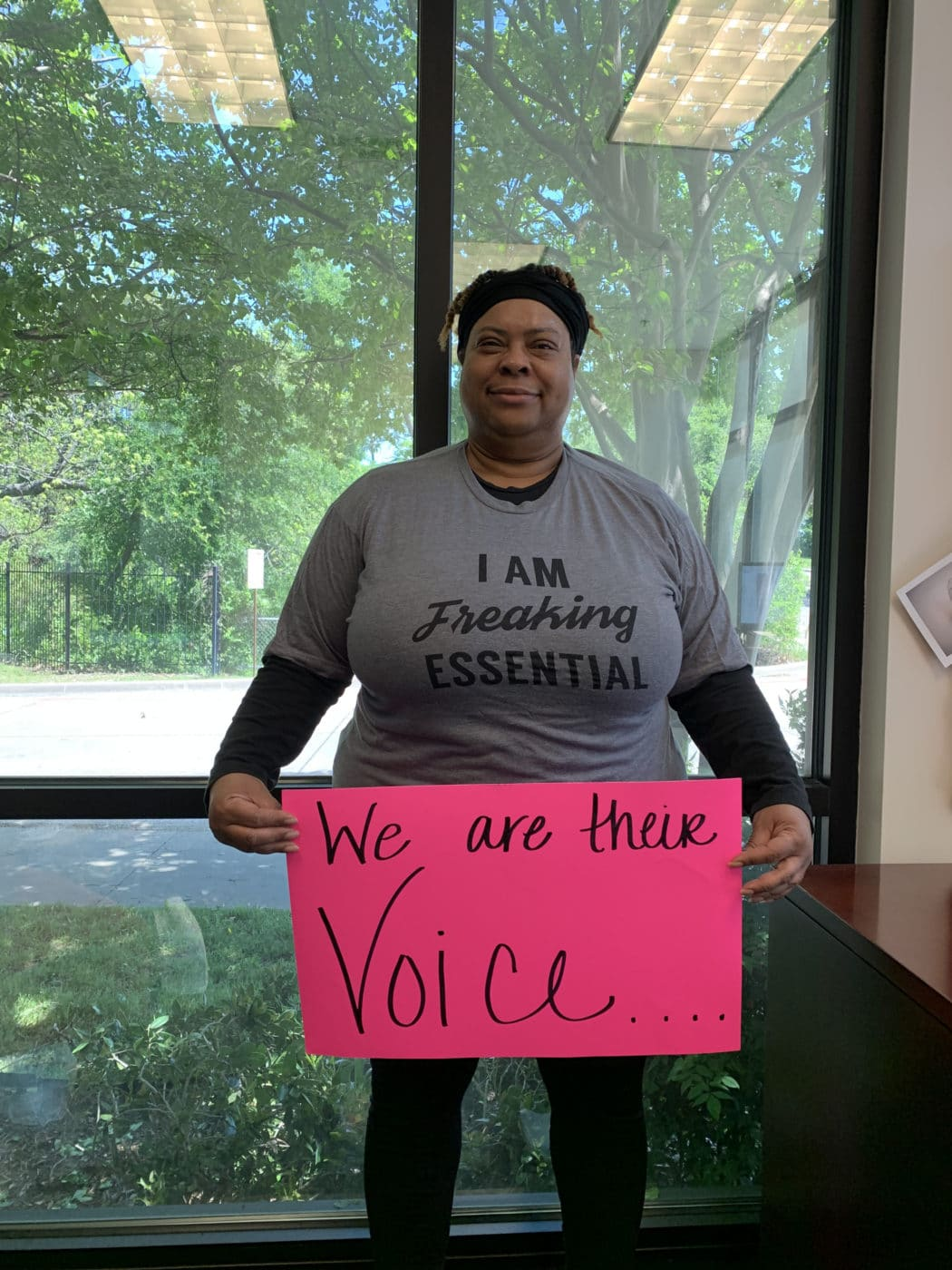 "Fredricka Cross holding a poster that says, ""We Are Their Voice"""