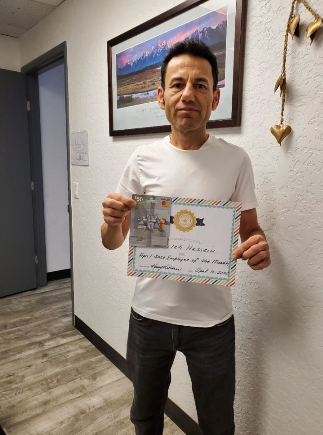 Saleh Hussien holding an award for 'Employee of the month'
