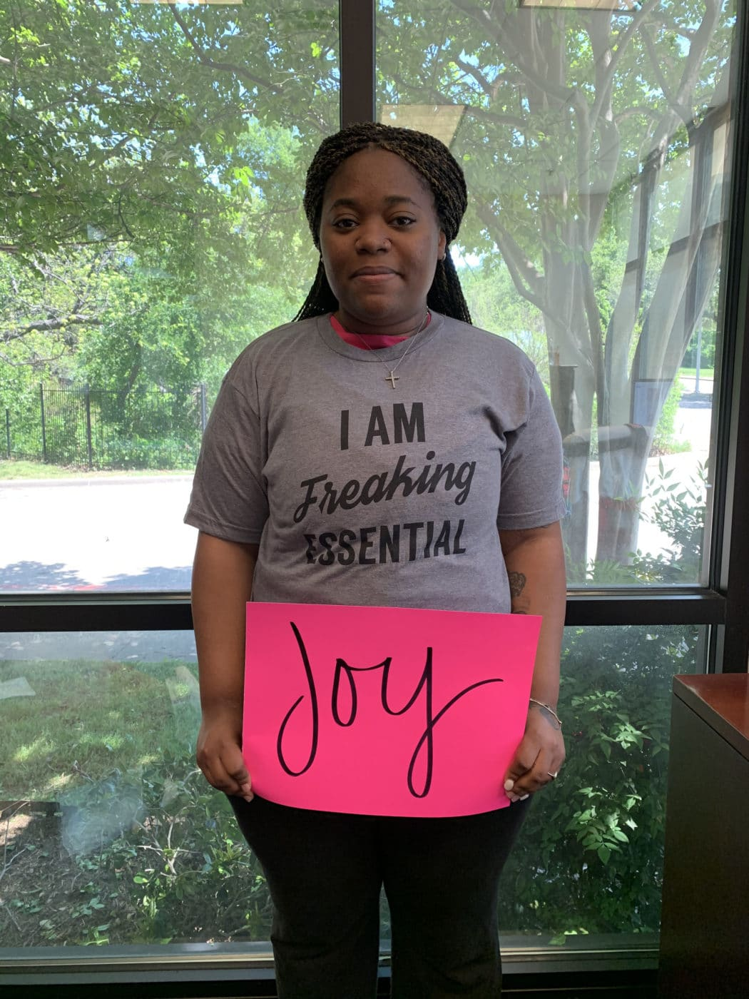 "Willisha Ewing holding up a poster that says, ""Joy"""