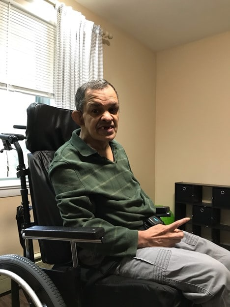 Edgardo, 60, Newton, New Jersey smiling and sitting in his wheelchair