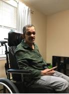 Edgardo sitting in his wheelchair smiling