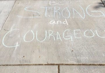 Be strong and courageous and other encouraging messages written with chalk on driveway.