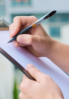 person holding a clipboard and a pen about to write